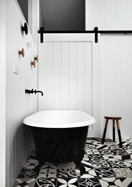 Cette photo montre une salle de bain tendance avec une baignoire sur pieds, un mur blanc, béton au sol et un sol multicolore.