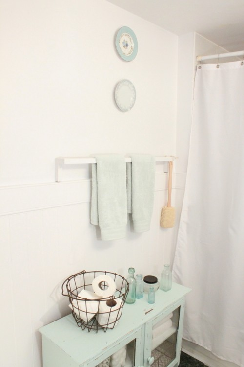 Bathroom with while walls and light green cabinet holding rolls of toilet paper and clean towels