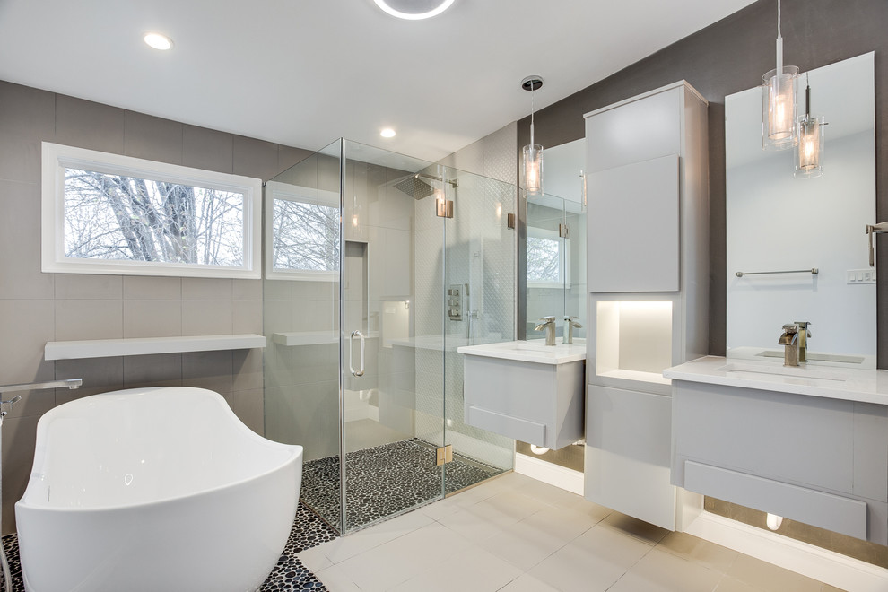 Example of a large minimalist master brown tile and porcelain tile porcelain tile and beige floor bathroom design in DC Metro with flat-panel cabinets, gray walls, an undermount sink, quartz countertops and a hinged shower door