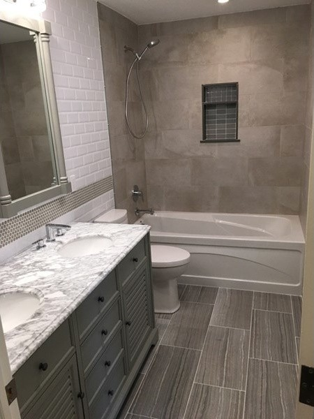 Mid-sized transitional master white tile and ceramic tile ceramic tile and gray floor bathroom photo in New York with gray cabinets, white walls, a drop-in sink, marble countertops, flat-panel cabinets and a two-piece toilet