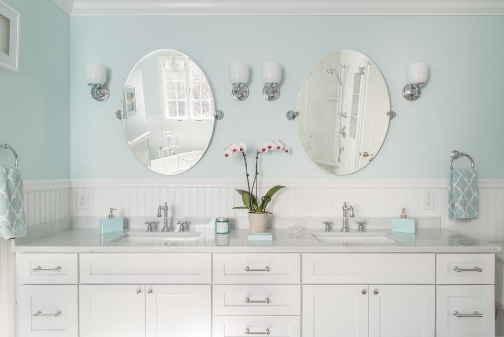 プロビデンスの中くらいのビーチスタイルのおしゃれなマスターバスルーム (シェーカースタイル扉のキャビネット、白いキャビネット、置き型浴槽、コーナー設置型シャワー、分離型トイレ、グレーのタイル、青い壁、磁器タイルの床、アンダーカウンター洗面器、大理石の洗面台、白い床、開き戸のシャワー、白い洗面カウンター) の写真