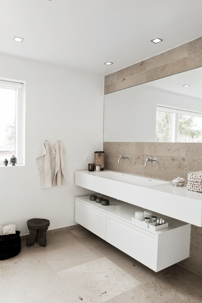Inspiration for a contemporary beige tile and stone tile bathroom remodel in West Midlands with an integrated sink, flat-panel cabinets, white cabinets and white walls