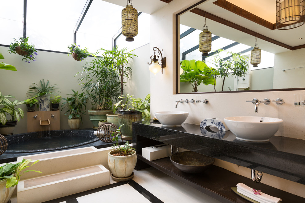 Inspiration for a tropical master drop-in bathtub remodel in Los Angeles with a vessel sink, open cabinets and beige walls