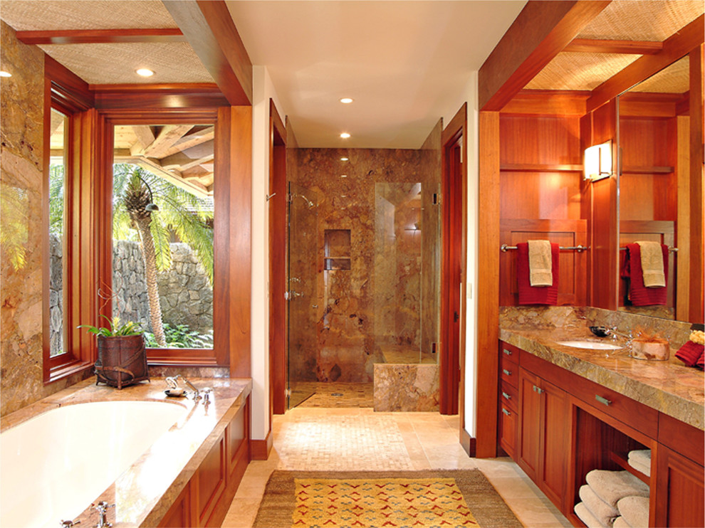Alcove shower - mid-sized tropical master brown tile and stone slab travertine floor and beige floor alcove shower idea in Hawaii with an undermount sink, shaker cabinets, medium tone wood cabinets, an undermount tub, white walls, a hinged shower door and gray countertops