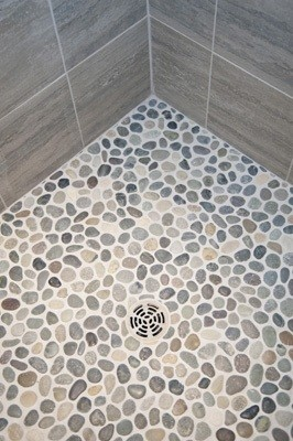 What is the name of the pebble floor tile and wall tile used? Love it!
