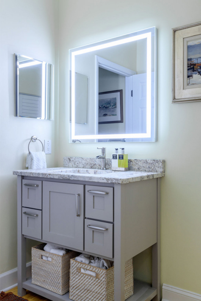 Inspiration for a small timeless 3/4 white tile and ceramic tile bamboo floor, brown floor and single-sink bathroom remodel in Atlanta with shaker cabinets, gray cabinets, a one-piece toilet, yellow walls, an undermount sink, granite countertops, beige countertops and a freestanding vanity