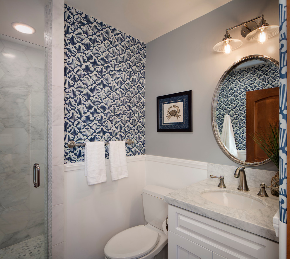 Alcove shower - small coastal 3/4 white tile and stone tile alcove shower idea in San Francisco with an undermount sink, raised-panel cabinets, white cabinets, marble countertops, a two-piece toilet and multicolored walls