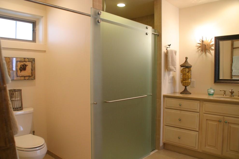 Immagine di una stanza da bagno con doccia stile marinaro di medie dimensioni con ante con bugna sagomata, ante bianche, doccia alcova, WC a due pezzi, piastrelle beige, piastrelle in ceramica, pareti beige, lavabo sottopiano, top in quarzo composito e porta doccia scorrevole