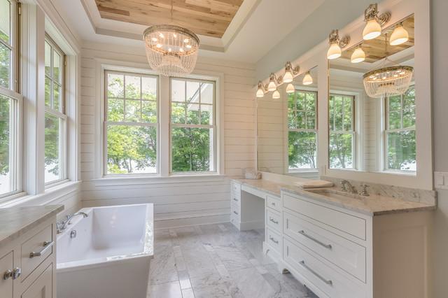 Inredning av ett lantligt badrum, med skåp i shakerstil, beige skåp, ett fristående badkar, vita väggar, marmorgolv, ett undermonterad handfat, marmorbänkskiva och grått golv