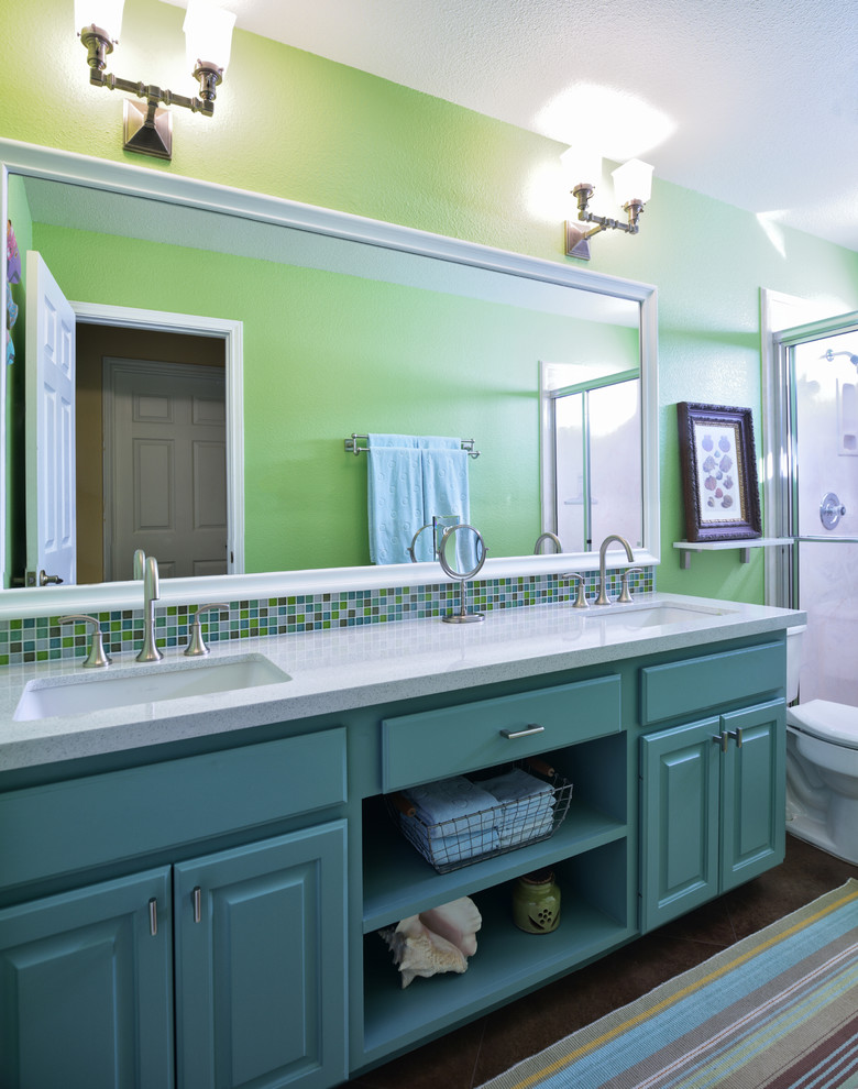 Example of a mid-sized classic 3/4 multicolored tile concrete floor alcove shower design in Austin with an undermount sink, raised-panel cabinets, turquoise cabinets, a two-piece toilet, quartzite countertops and green walls