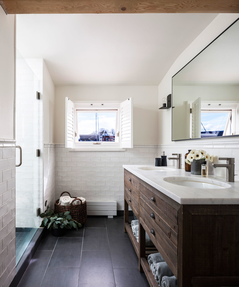 Beach style white tile and subway tile black floor alcove shower photo in Seattle with furniture-like cabinets, dark wood cabinets, white walls, an undermount sink, a hinged shower door and white countertops