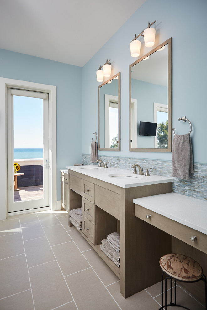 Example of a beach style master multicolored tile and mosaic tile bathroom design in Grand Rapids with open cabinets, light wood cabinets, blue walls and an undermount sink