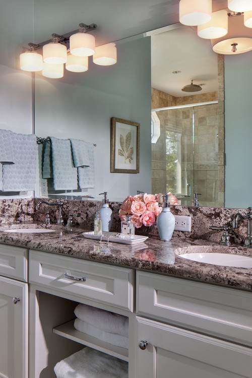A classic, traditional styled bathroom and white vanity with granite countertops.