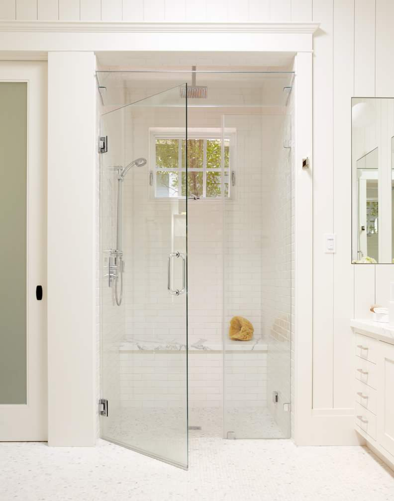 Large white tile shower with bench, steam shower, and window for natural light