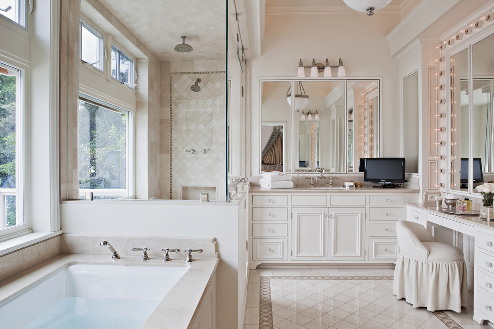 Elegant beige tile white floor alcove shower photo in Los Angeles with recessed-panel cabinets, white cabinets and an undermount tub