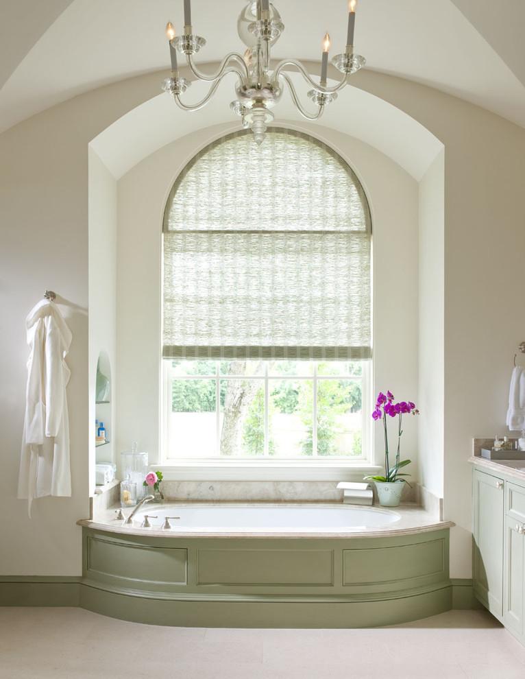 Alcove bathtub - traditional beige tile alcove bathtub idea in Dallas with recessed-panel cabinets and green cabinets