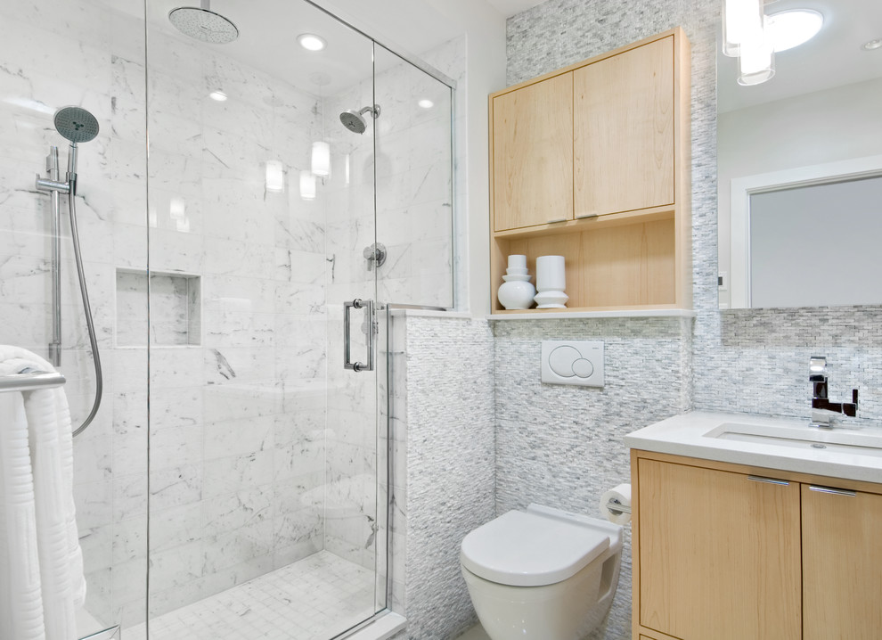 Example of a small trendy white tile and stone tile porcelain tile bathroom design in Ottawa with an undermount sink, flat-panel cabinets, light wood cabinets, quartz countertops, a wall-mount toilet and gray walls