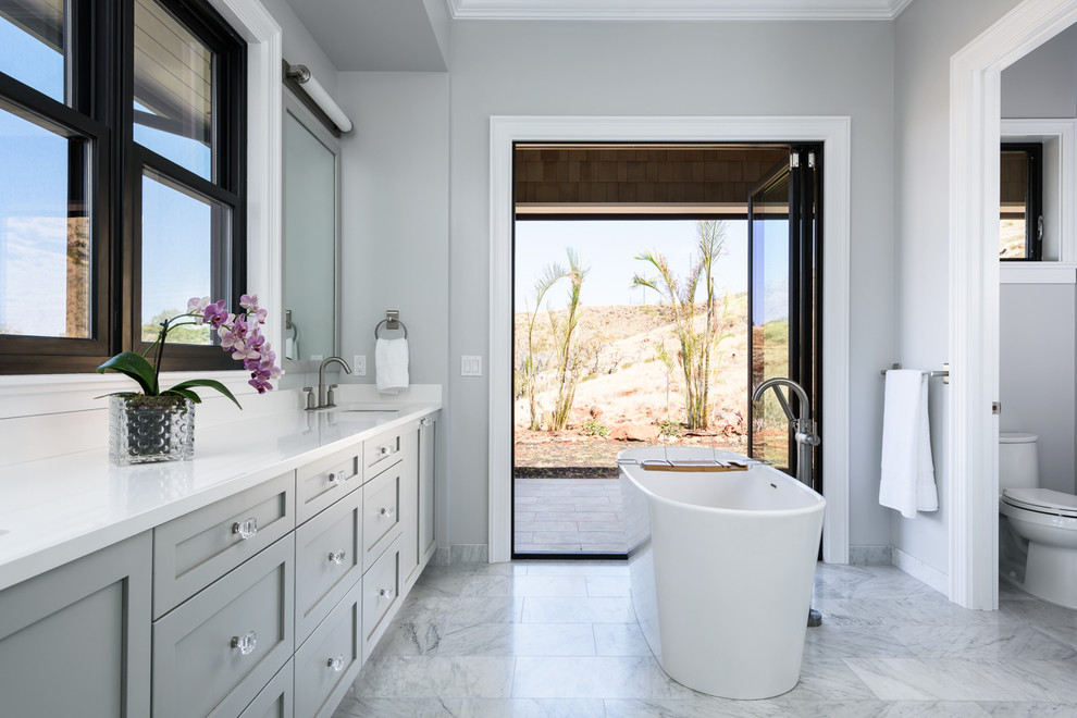 Inspiration for a large transitional master marble floor freestanding bathtub remodel in Hawaii with shaker cabinets, gray cabinets, a one-piece toilet, gray walls, an undermount sink and quartz countertops