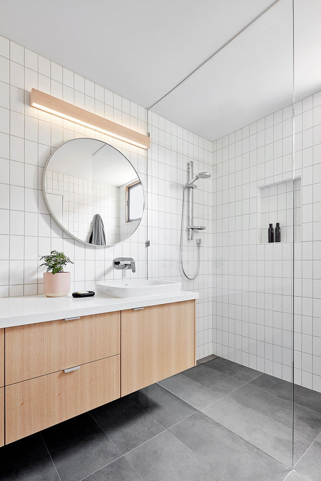 Inspiration for a beach style bathroom in Melbourne with flat-panel cabinets, light wood cabinets, a curbless shower, white tile, a drop-in sink and grey floor.