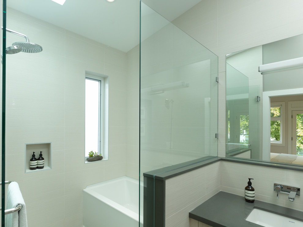 Inspiration for a contemporary white tile and ceramic tile ceramic tile bathroom remodel in Vancouver with an undermount sink, flat-panel cabinets, light wood cabinets, granite countertops, a wall-mount toilet and gray walls