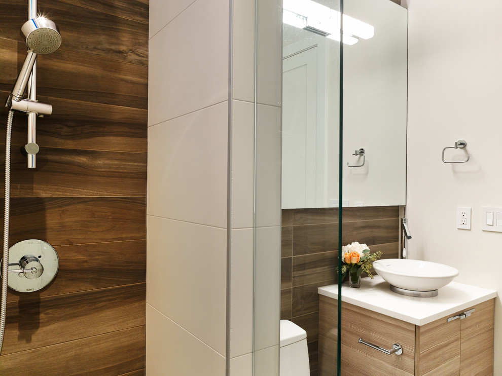Example of a trendy brown tile and ceramic tile ceramic tile bathroom design in Vancouver with a vessel sink, light wood cabinets, quartz countertops, a one-piece toilet and beige walls