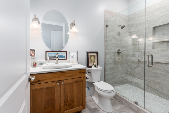 Small elegant 3/4 gray tile gray floor bathroom photo in Salt Lake City with a two-piece toilet, gray walls, engineered quartz countertops, white countertops, recessed-panel cabinets, medium tone wood cabinets and a drop-in sink