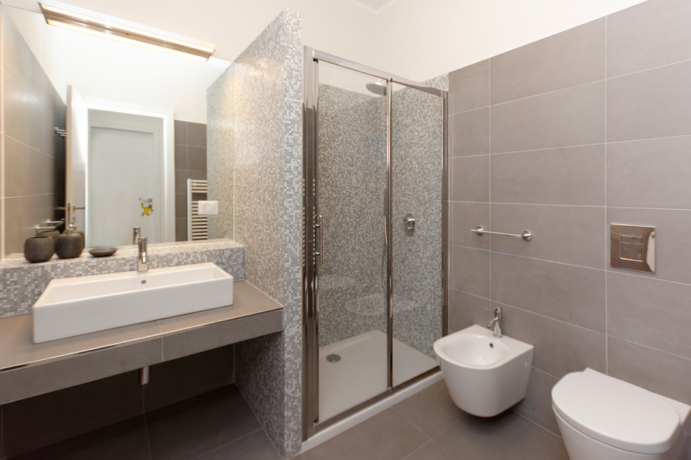 Mid-sized trendy master gray tile and ceramic tile ceramic tile corner shower photo in Milan with a console sink, tile countertops, a wall-mount toilet and white walls