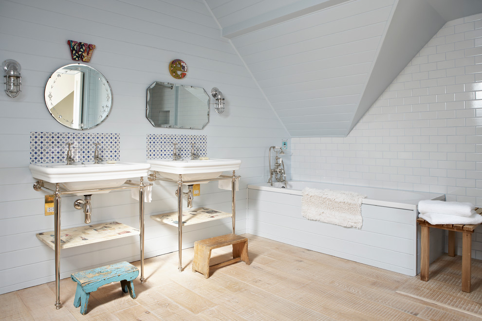 Cottage chic white tile and subway tile light wood floor drop-in bathtub photo in London with a console sink and white walls