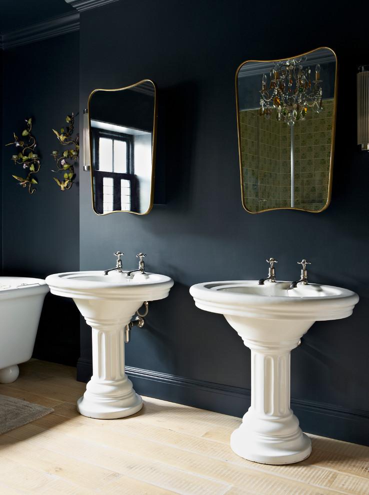 Elegant light wood floor bathroom photo in London with a pedestal sink and black walls
