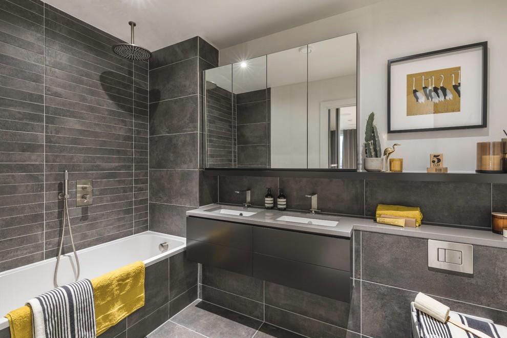 Foto de cuarto de baño contemporáneo con armarios con paneles lisos, puertas de armario grises, bañera encastrada, combinación de ducha y bañera, sanitario de pared, baldosas y/o azulejos grises, paredes grises, suelo de azulejos de cemento, aseo y ducha, lavabo bajoencimera, encimera de cemento, suelo gris, ducha abierta y encimeras grises