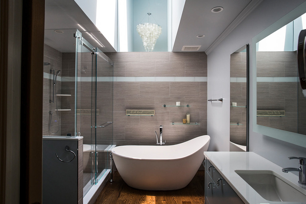 Example of a mid-sized trendy master brown tile medium tone wood floor and brown floor bathroom design in New York with flat-panel cabinets, gray cabinets, gray walls and an undermount sink
