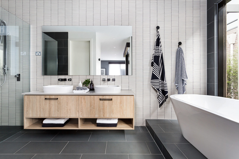 This is an example of a contemporary bathroom in Melbourne with a freestanding tub, grey floor, flat-panel cabinets, light wood cabinets, white tile and a vessel sink.