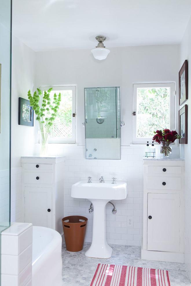 ロサンゼルスのビーチスタイルのおしゃれなお風呂の窓 (ペデスタルシンク、シェーカースタイル扉のキャビネット、白いキャビネット、置き型浴槽、白いタイル、サブウェイタイル、白い壁) の写真
