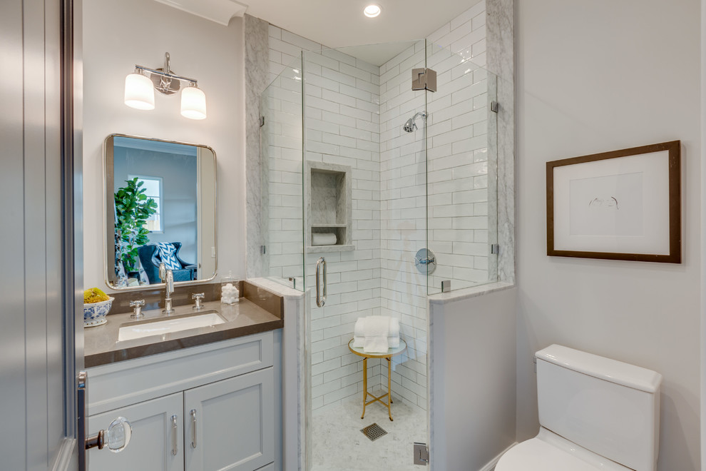 Inspiration for a small transitional 3/4 white tile alcove shower remodel in Los Angeles with recessed-panel cabinets, white cabinets, white walls, an undermount sink, a hinged shower door and brown countertops