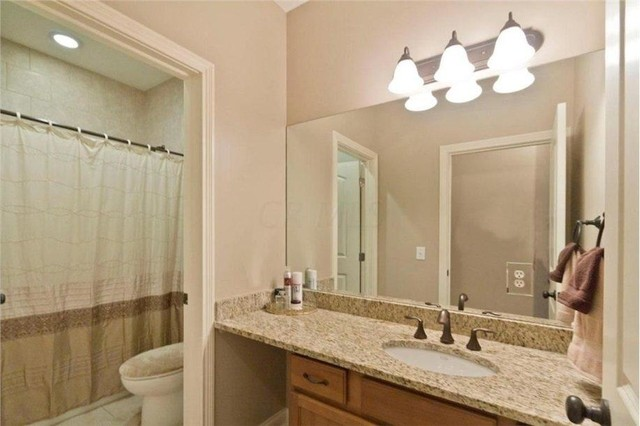Bathroom - large traditional kids' beige tile and ceramic tile ceramic floor bathroom idea in Columbus with an undermount sink, recessed-panel cabinets, light wood cabinets, granite countertops, a two-piece toilet and beige walls