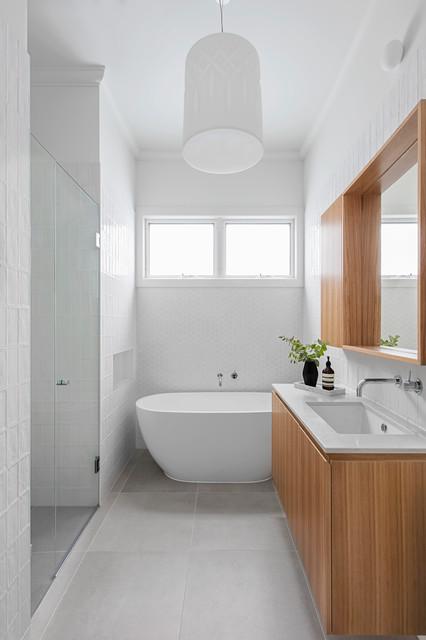 Exempel på ett mellanstort modernt badrum, med skåp i mellenmörkt trä, ett fristående badkar, vit kakel, klinkergolv i porslin, ett undermonterad handfat, bänkskiva i kvarts, grått golv, dusch med gångjärnsdörr och vita väggar