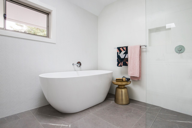 This is an example of a large contemporary master bathroom in Sydney with shaker cabinets, white cabinets, a freestanding tub, an open shower, a wall-mount toilet, white tile, porcelain tile, white walls, porcelain floors, an integrated sink, engineered quartz benchtops, grey floor, an open shower and white benchtops.