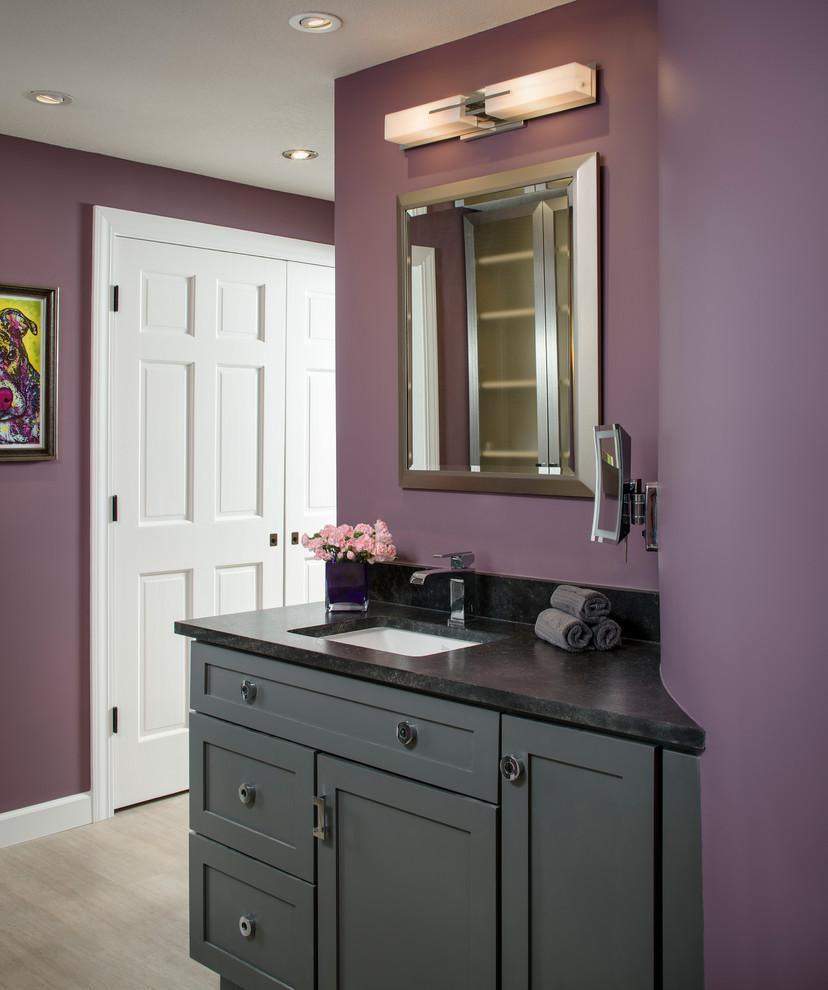 Diseño de cuarto de baño principal, actual, grande, con armarios estilo shaker, puertas de armario grises, bañera exenta, ducha a ras de suelo, sanitario de una pieza, paredes púrpuras, lavabo bajoencimera, encimera de granito, baldosas y/o azulejos beige, baldosas y/o azulejos de mármol, suelo de madera clara, suelo beige y ducha abierta