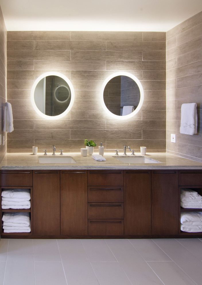 Trendy gray tile and ceramic tile bathroom photo in Los Angeles with an undermount sink, flat-panel cabinets, dark wood cabinets and limestone countertops