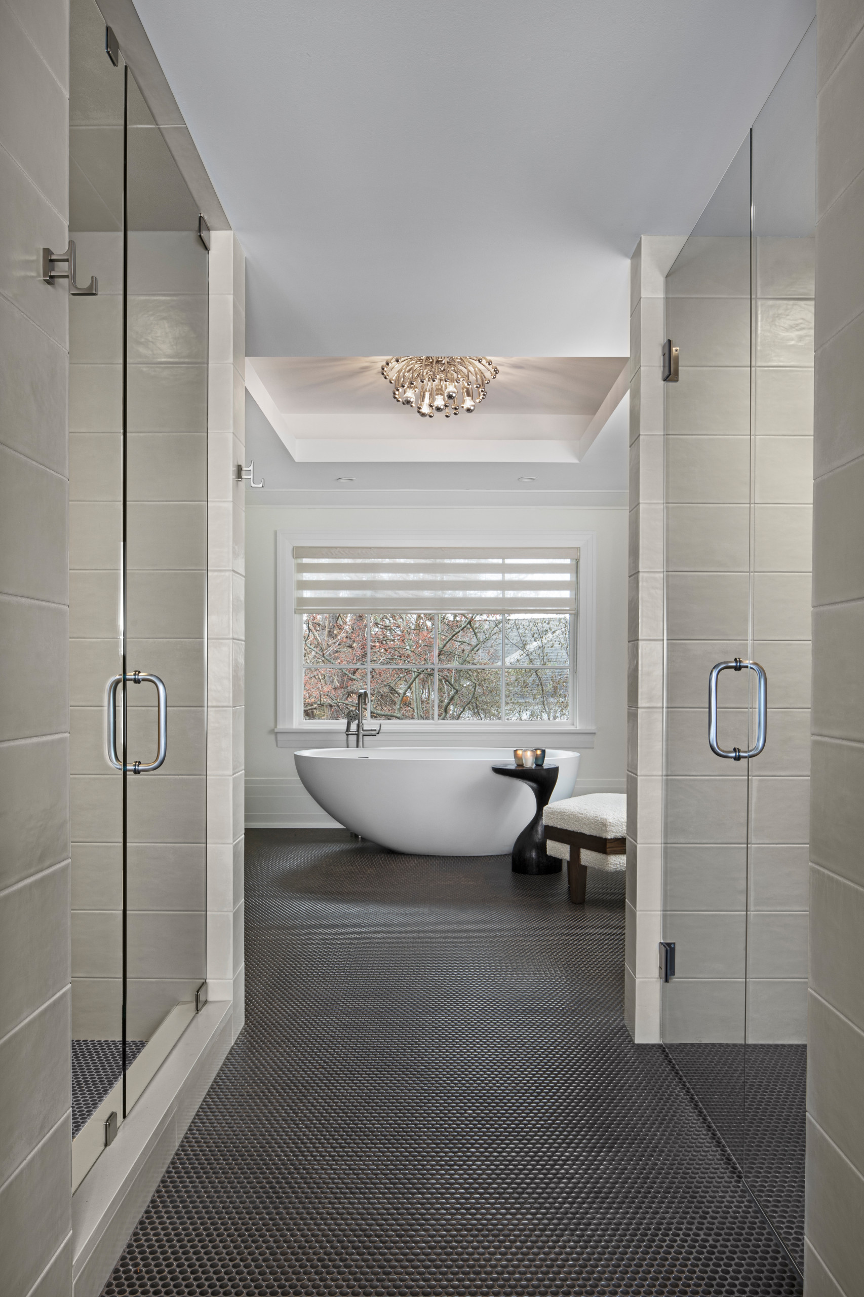 The experience of entering the master bath for Her is one filled with elegance and drama. The copper penny round tile floor leads past a pair of Euro Glass doors, with a shower room to the left and a