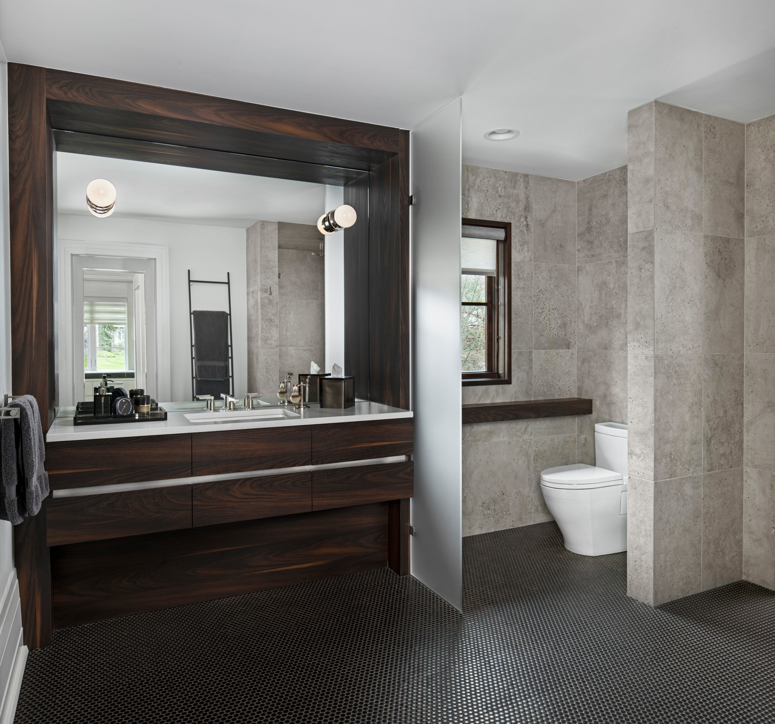 This custom vanity is the perfect place for Him to unwind after a long day. A wood surround and recessed panel below highlight the vanity drawers, which are separated by a stainless reveal across each