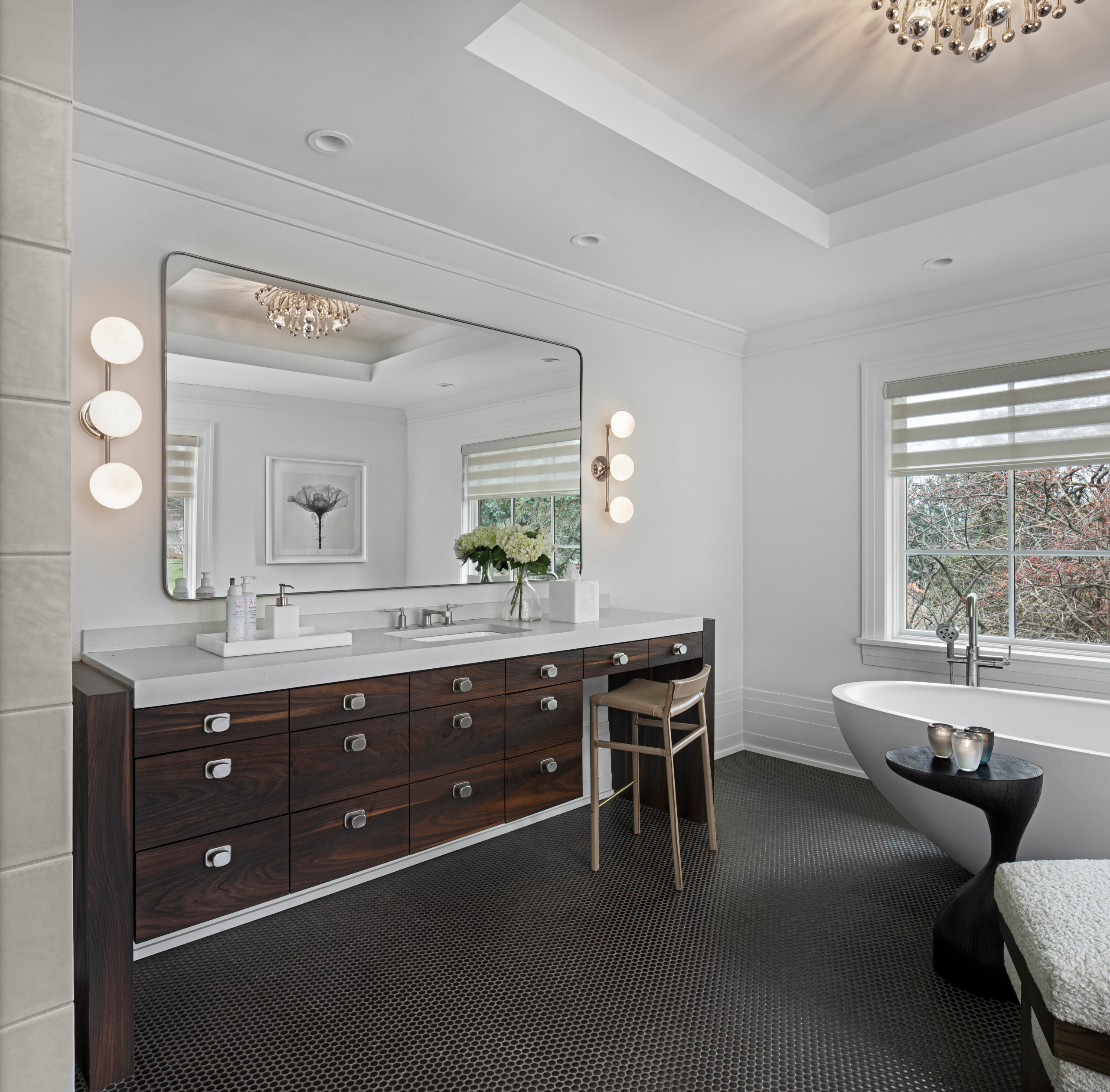"""This custom makeup and bath vanity become a beautiful focal point for the room. Larger bulkheads on each end frame the vanity, and a 2"""" mitered quartz countertop nestles between the book ends. Each an"""