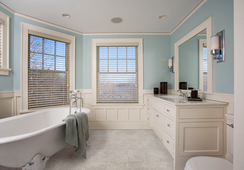 Inspiration for a mid-sized timeless master white tile freestanding bathtub remodel in Toronto with a drop-in sink, recessed-panel cabinets, beige cabinets, marble countertops, a one-piece toilet and blue walls