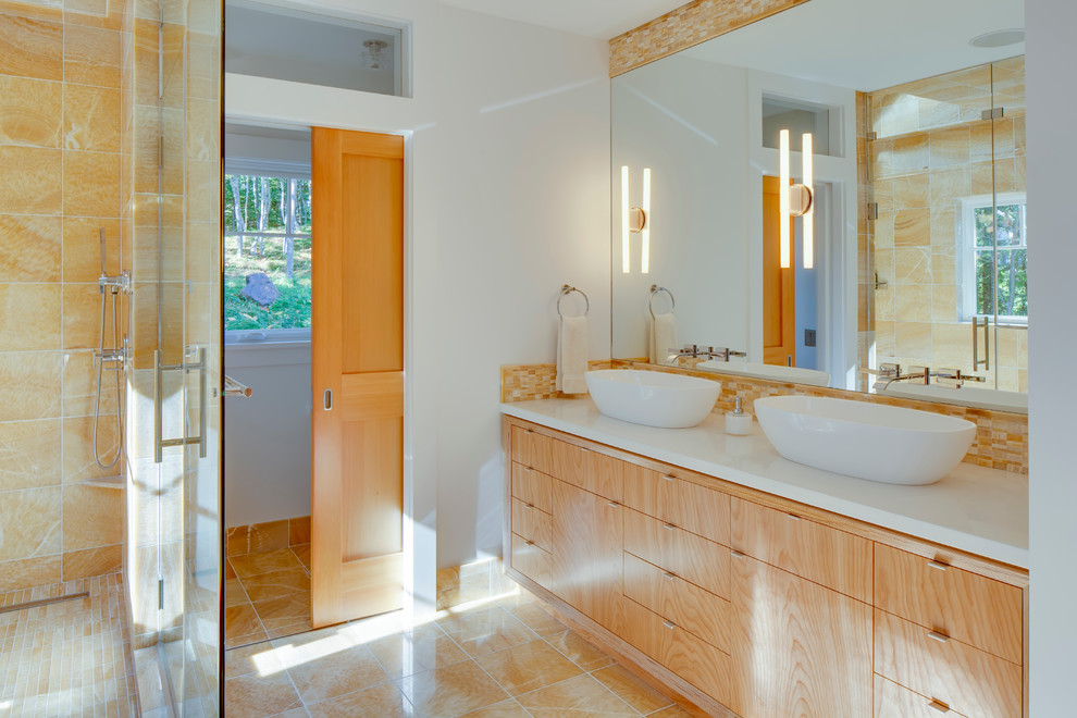 Example of a large trendy master beige tile and porcelain tile marble floor bathroom design in Portland Maine with a vessel sink, flat-panel cabinets, light wood cabinets, a one-piece toilet, beige walls and solid surface countertops