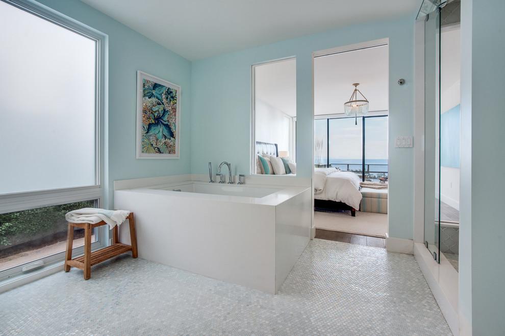 Modelo de cuarto de baño principal, marinero, sin sin inodoro, con armarios con paneles lisos, puertas de armario de madera clara, baldosas y/o azulejos de vidrio laminado, paredes azules, lavabo encastrado, encimera de cuarzo compacto, bañera encastrada sin remate y baldosas y/o azulejos blancos
