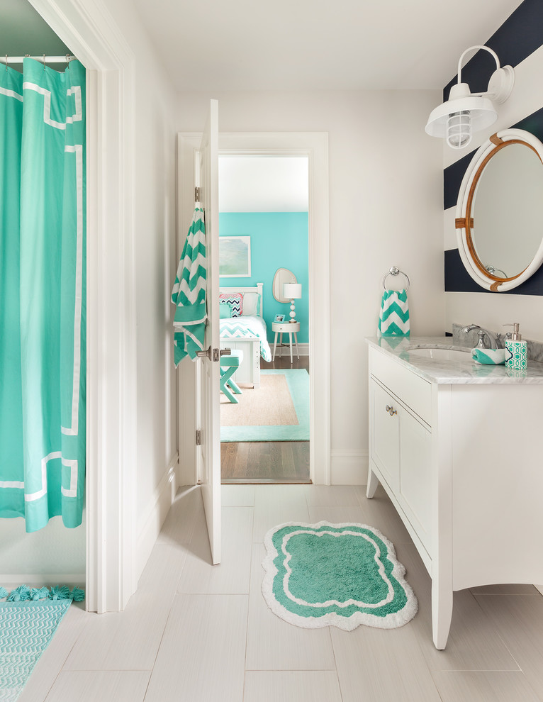 Example of a mid-sized transitional kids' white tile and ceramic tile porcelain tile bathroom design in New York with shaker cabinets, white cabinets, a two-piece toilet, an undermount sink, marble countertops and multicolored walls