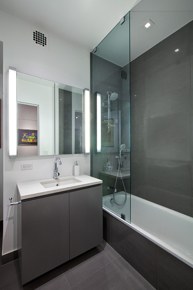 Example of a trendy gray tile and ceramic tile bathroom design in New York with flat-panel cabinets and gray cabinets