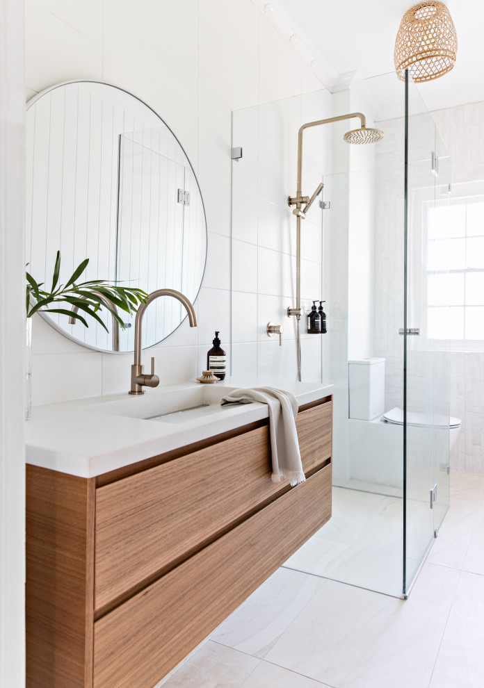 This is an example of a contemporary 3/4 bathroom in Sydney with flat-panel cabinets, medium wood cabinets, a curbless shower, a two-piece toilet, white tile, an integrated sink, white floor, a hinged shower door and white benchtops.