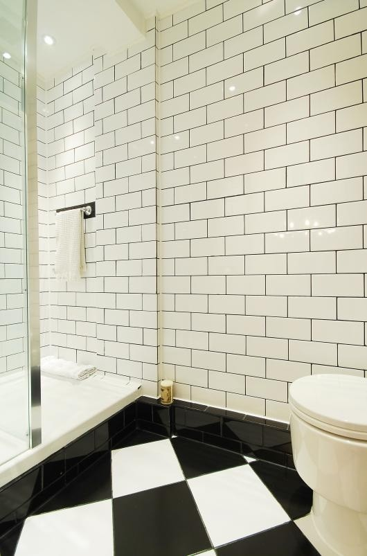 Inspiration for a small modern black tile and ceramic tile ceramic tile doorless shower remodel in London with a console sink, flat-panel cabinets, black cabinets, tile countertops, a one-piece toilet and white walls