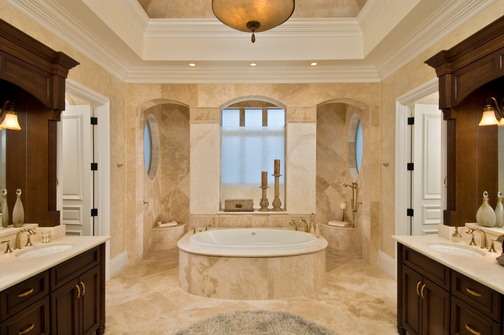 Example of an island style beige tile drop-in bathtub design in Miami with an undermount sink, recessed-panel cabinets and dark wood cabinets